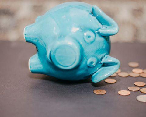 Blue piggy bank falling over