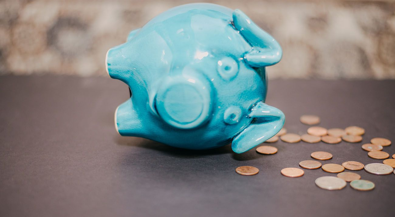 Blue piggy bank falling over