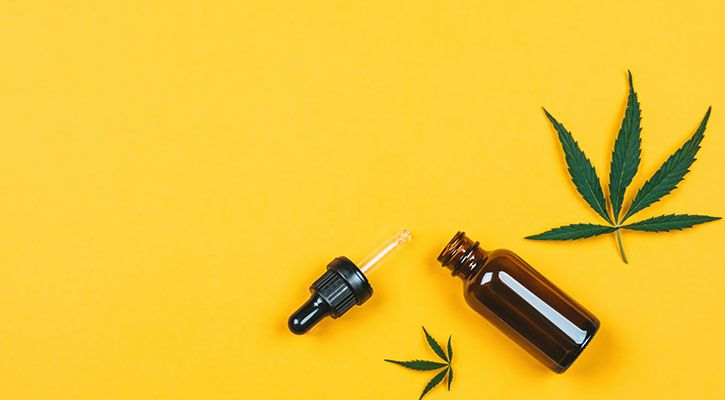 Cannabis leaf and cbd oil on a yellow backdrop