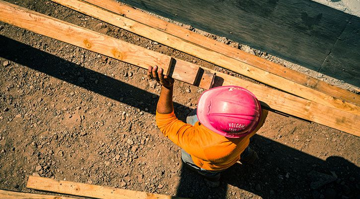 Worker at a construction site carrying wood blocks