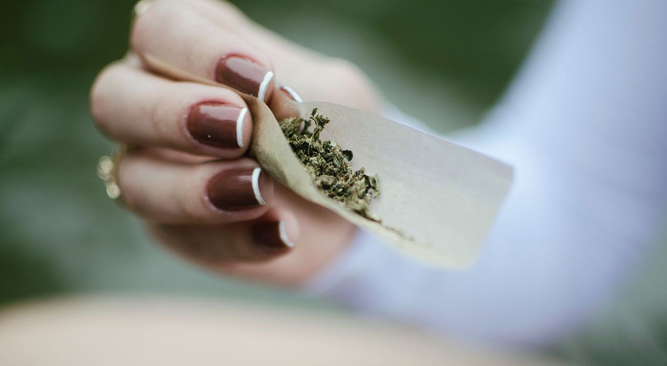 Australian woman rolling a cannabis joint
