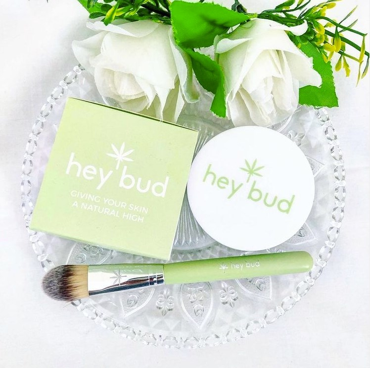 Hey Bud skincare on a plate with white roses